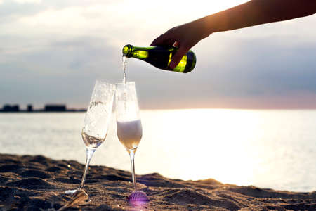 Woman hand pouring champagne into glasses on golden beach of azure calm Spanish seashore with waves in summer sunset or sunrise time. bottle and two glasses on sand in the morning. Starting a New day