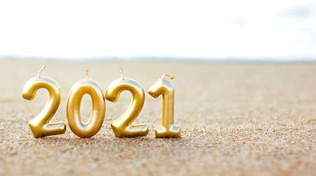 Yellow figure of the numbers of new year 2021 in the sand on the beach against the backdrop of the sea. First day of the new year. Space for text. Spend Holidays and celebration on the beach concept