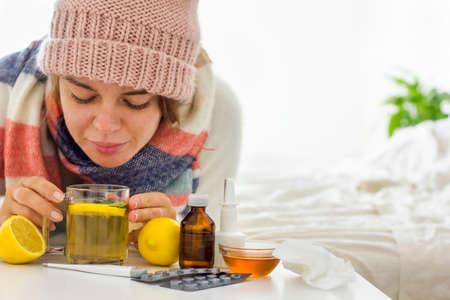 Close up a warmly dressed with hat and scarf young woman laying in bed and drinking hot tea with lemon and another medicine. Seasonal colds and diseases. Home treatment.