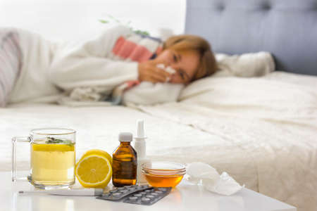 Selective focus on alternative medicine on the night table (hot drink, lemon, honey, pills, thermometer, nasal spray and crumpled handkerchiefs. Young sick woman laying on bed