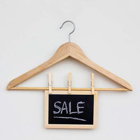 empty clothes hanger on light background with sale sign