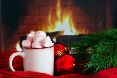 Cozy scene near fireplace with a white enameled mug with hot drink with marshmallow next to red christmas balls and xmas tree branch on cozy warm red scarf. Christmas mood and atmosphere. Winter holiday concept Standard-Bild