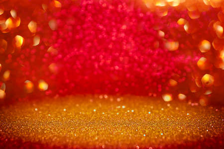 Gold and red abstract glitter background with selective focus. Red and yellow defocused bokeh lights. Christmas xmas, New Year Eve or St. valentine day background. Celebration event