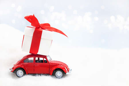 Retro Toy red Car With Christmas Gift white box with red ribbon and bow carrying on the roof on white background with space for text. Xmas and Happy new year delivery concept. Banco de Imagens