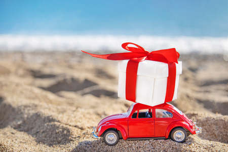 White gift with a red ribbon stands on the roof of a toy car on the sand on the beach. Gift delivery anywhere in the world. Holidays on the beach with sea