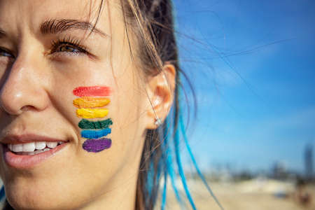 Close up portrait of a smiling beautiful young woman with rainbow flag painted on her face. Copy space. and rights. Outdoors