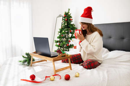 Online christmas and new year celebration concept. online party and family congratulations. online shopping. Woman with notebook computer at home in Santa hat with gift box. Winter holidays sales