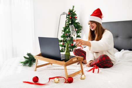 Online christmas and new year celebration concept. Woman with notebook computer at home in Santa hat drinking champagne. social distance, remote communication, online party and family congratulations