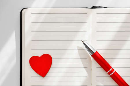 Top view notebook with red heart shape and pen on it. Plan of the day, to-do list Valentine day concept. Leave a message.