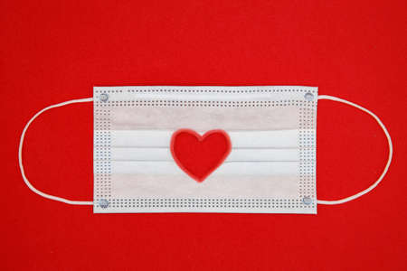 Top view Medical protective face mask with red heart shape on reg background. Valentines Day concept, stay safe. cut out heart shape Flatlay