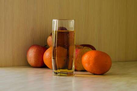 citrus fruits: glass of juice, apples and tangerines, simple background