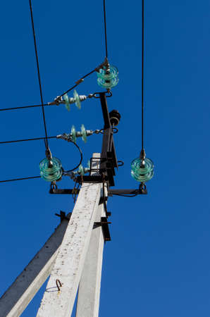 volte: concrete pole with electrical insulators and wires on a background of blue sky