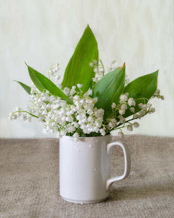 rustical: Bouquet of white lily-of-the-valley on the simple rustical background.