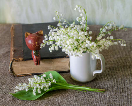 wooden figure: Still life with lily-of-the-valley, old book and wooden figure