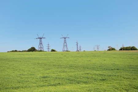 electric columns on a green field Stock Photo
