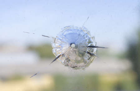 crazed: The round hole, is probable from shot, in old dirty glass