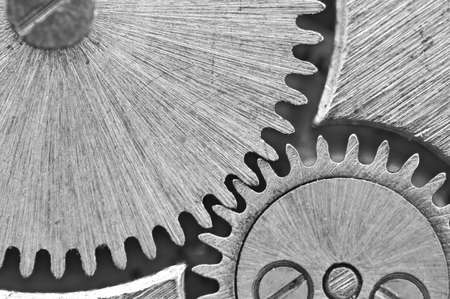 Macro, Zwarte witte achtergrond met metalen tandraderen een uurwerk. Conceptuele foto voor uw succesvolle business ontwerp