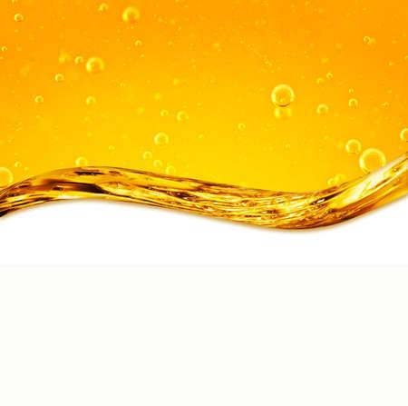 El líquido fluye amarillo, para el proyecto, aceite, miel, cerveza u otras variantes en el fondo blanco, área para el texto Foto de archivo