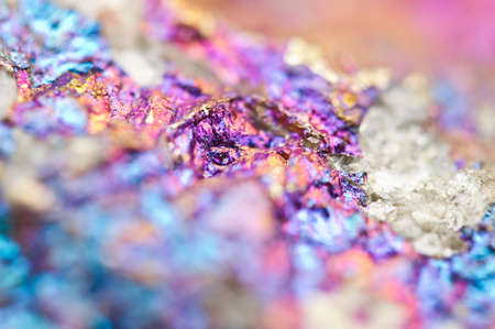 Bornite ore crystallizes mineral its blurred natural background. Macro. Focus on the central. Very shallow depth of field
