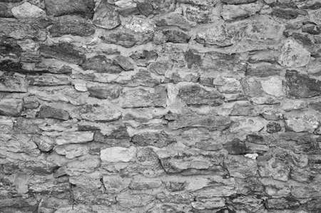 Black-and-white Texture of an old stone wall. Closeup