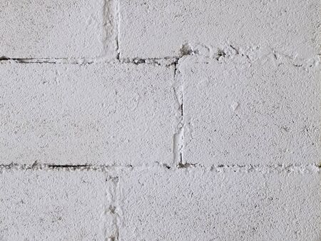 brickwork wall covered with coarse white plaster