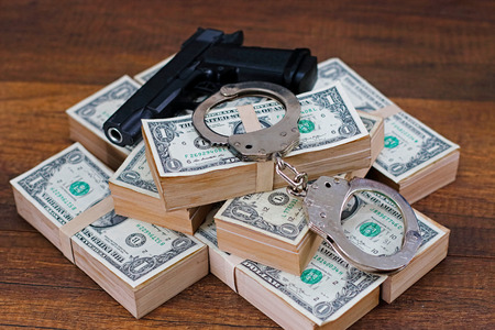Handcuffs, money and gun on wooden table