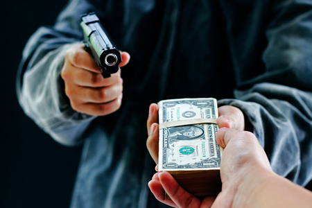 Robber used the gun to robbery the money Stockfoto