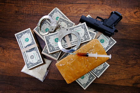 Drugs, Handcuffs, Gun, money and syringes on wooden table