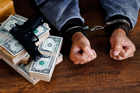 Man in Handcuffs with Drugs, money and gun on wooden table