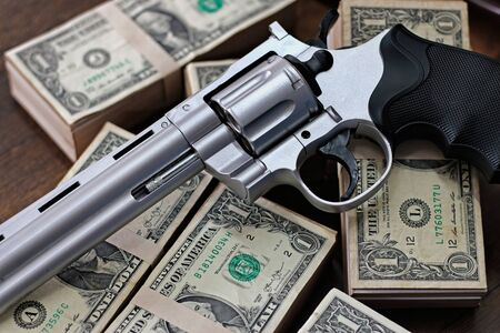Money and gun on wooden table. Concept of crime. Stock Photo