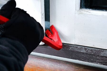 Burglar with crowbar trying break the door to enter the house Reklamní fotografie