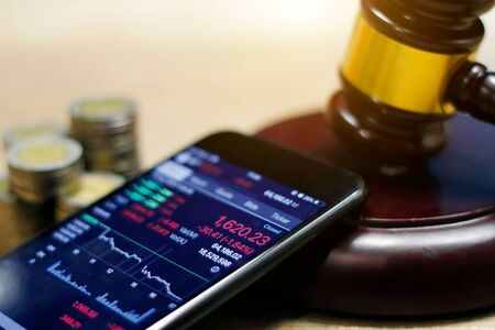 Smartphone showing stock market trend and Judge gavel, coin on table Stock Photo