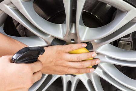 Hand applying polish car wheel