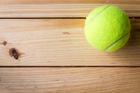 Tennis ball on a wooden table