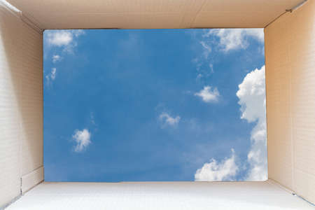 Inside of brown cardboard box with blue sky background