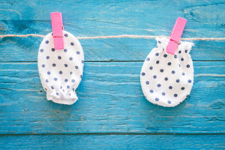 Baby gloves on a wooden background