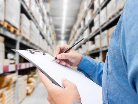 man contrôle liste sur presse-papiers dans un entrepôt Banque d'images