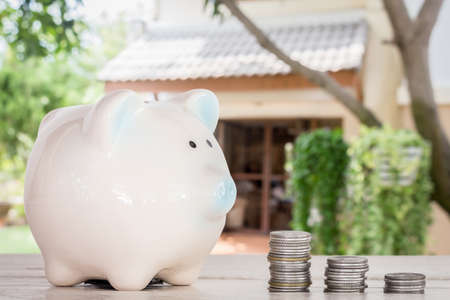 pay raise: Piggy bank and coins on home blur background