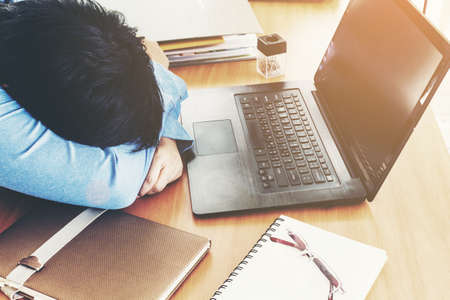 Businessman sleeping at work with laptop at office desk Stock Photo