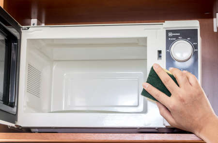 Hand cleaning outside of microwave oven Imagens