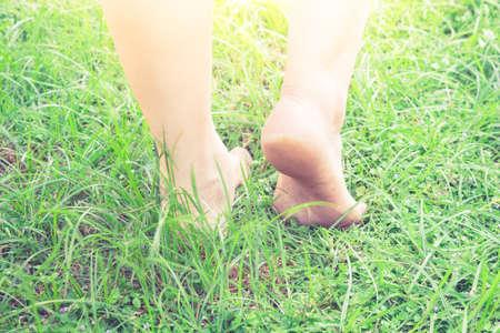 Female legs walking on green grass