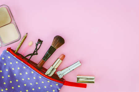 Make up bag with cosmetics on pink background Foto de archivo