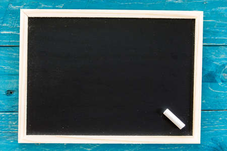 Wooden framed blank blackboard with a  chalk on wooden background Stock Photo