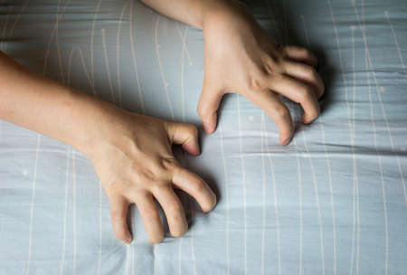 Woman hand grasping on bed sheet