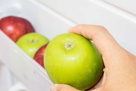 Hand holding apples in refrigerator ideal for diet