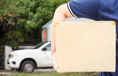 Delivery man in blue uniform holding the box Stock Photo