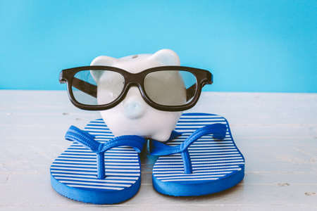 Piggy bank with sunglasses on wooden table Stock Photo
