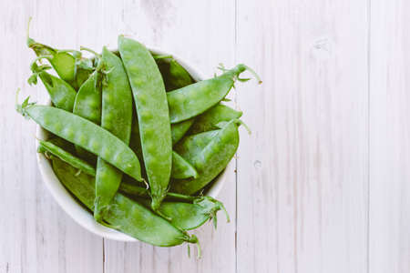 Green pea in bowl on  wooden background
