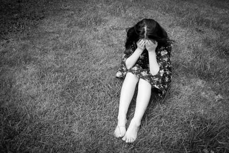 Sad woman sitting close her face on grass