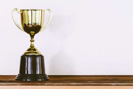 Golden trophy on wooden table with copy space